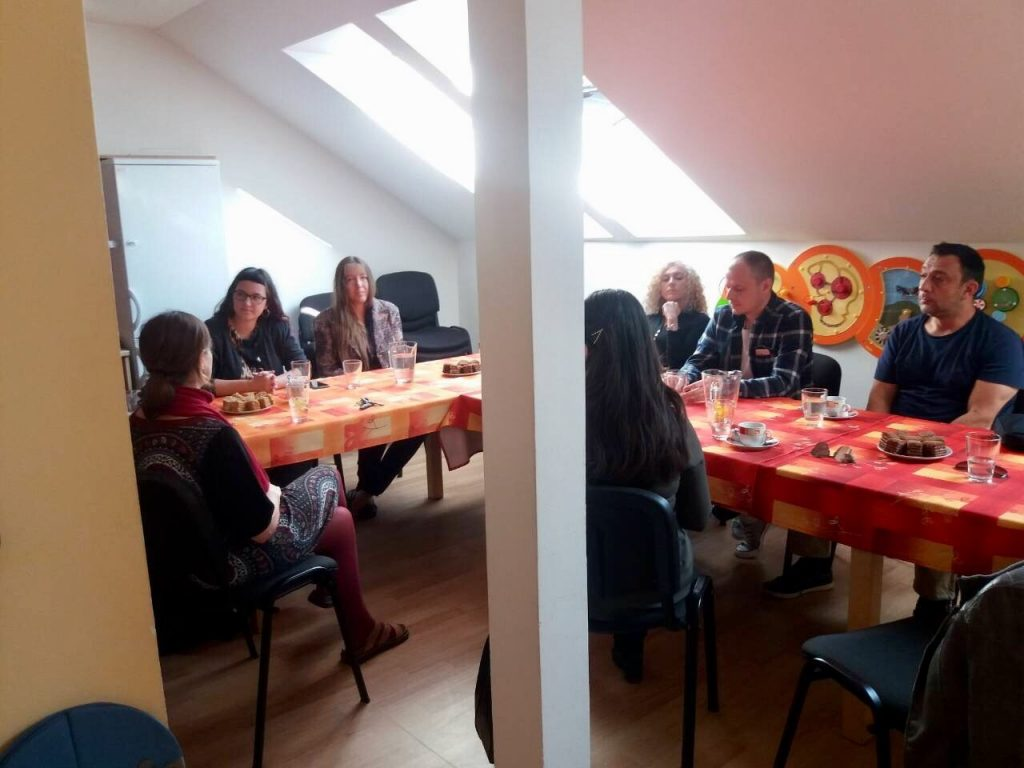 Seven people sitting indoor around a table.