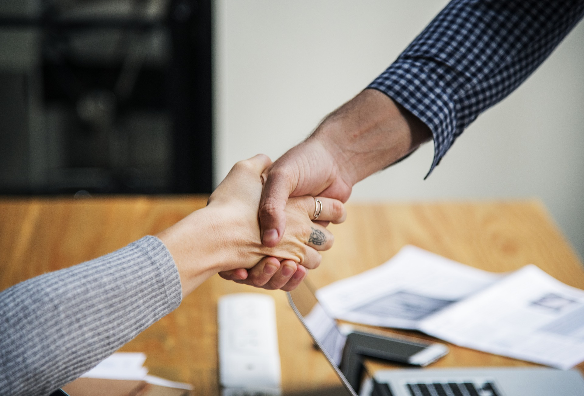 Two hands handshaking above an office desk illustrating business partners.