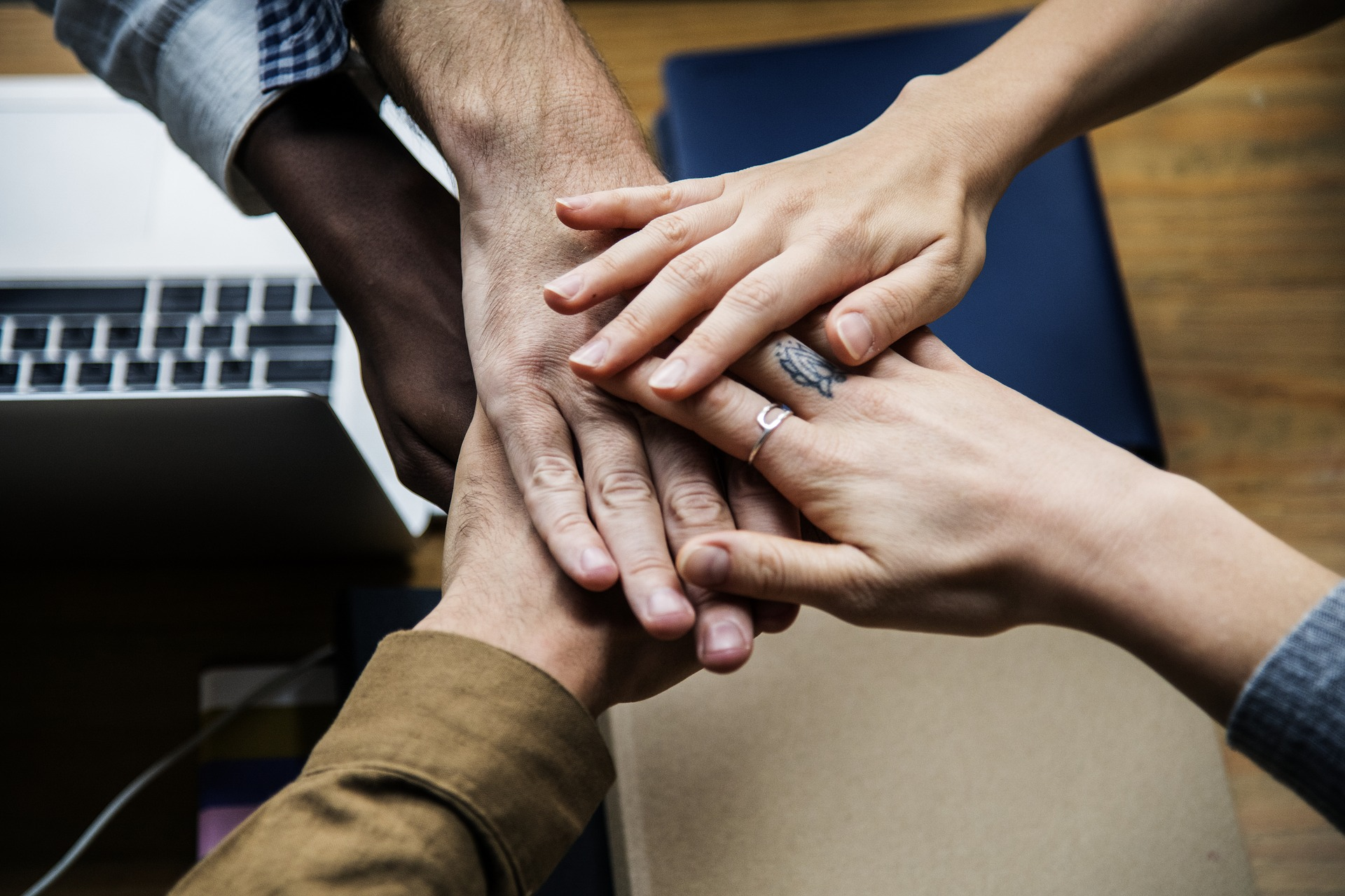 Five hands held together above an office desk illustrates social inclusion.