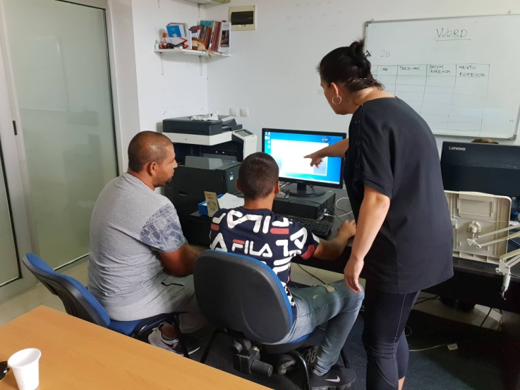 Two people sitting behind a computer indoor while the teacher is standing and pointing at the screen.