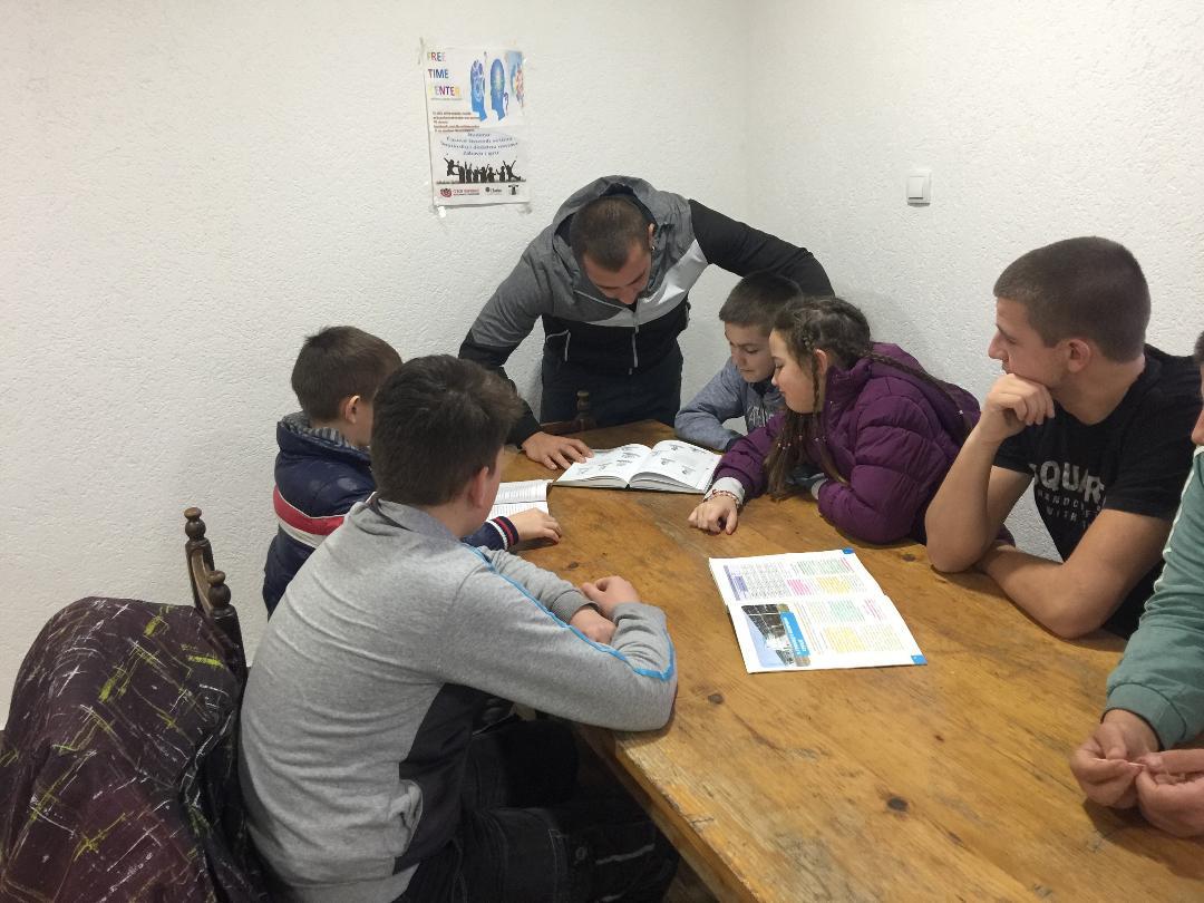Teacher helping a group of six kids do their homework.