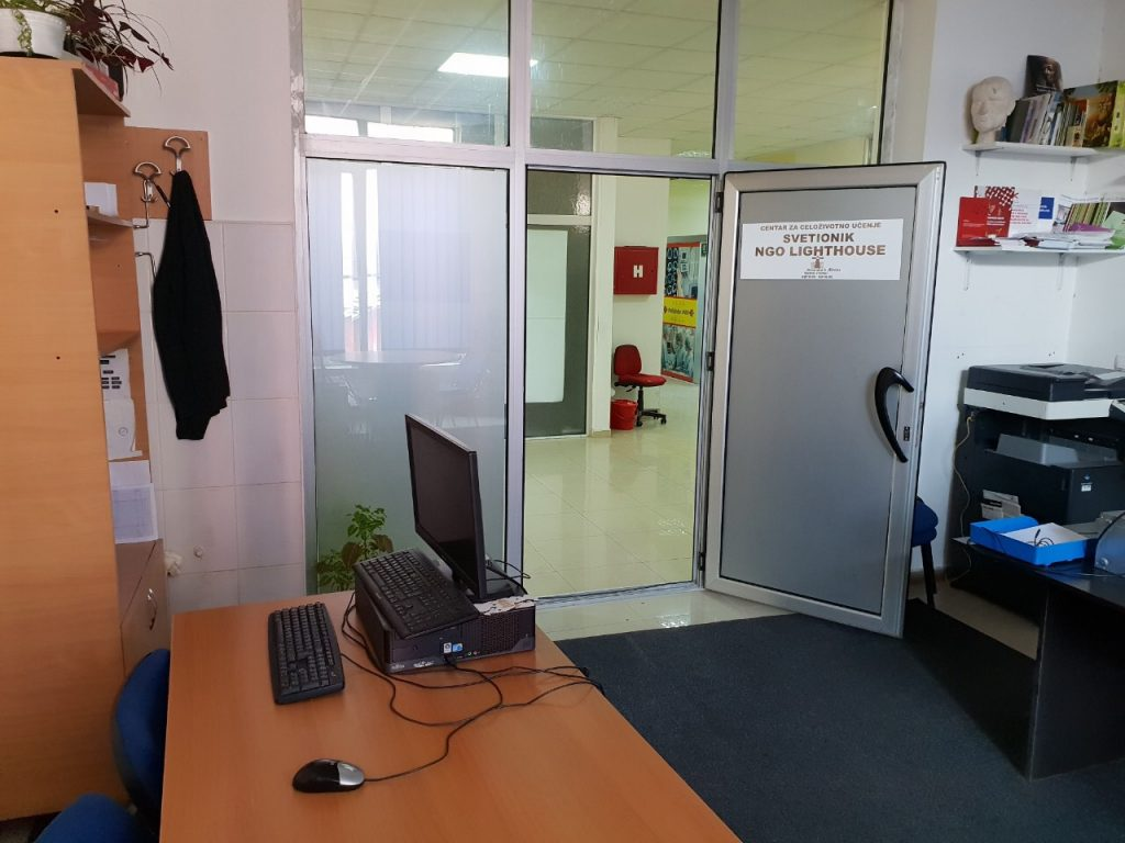 Desk with a screen in an office and opened door.