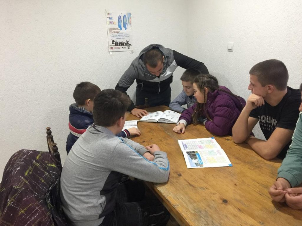 Teacher helping a group of six kids do their homework.