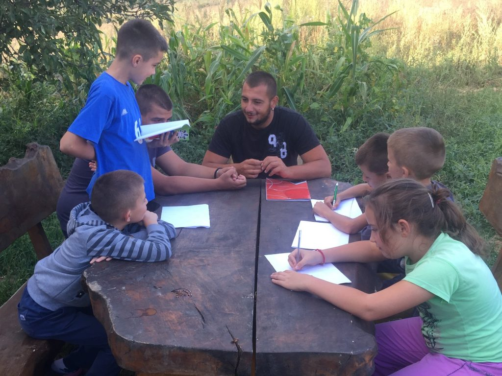 Teacher sitting with students outdoor at a wooden table while they do their homework.