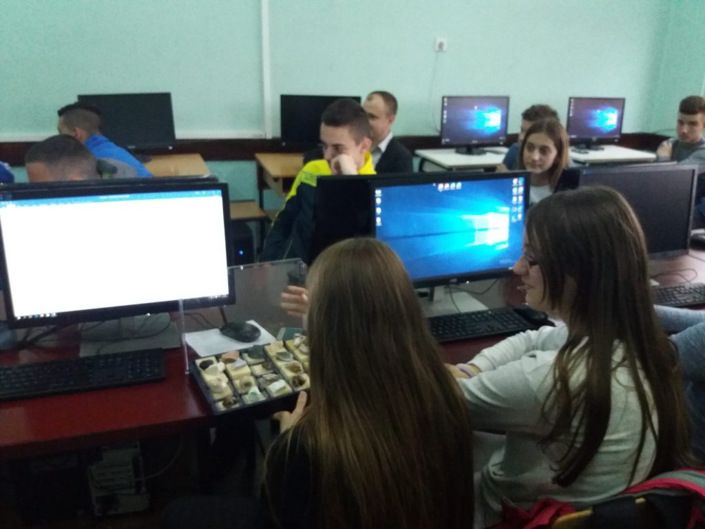 Nine students sitting behind computer screens in a classroom.