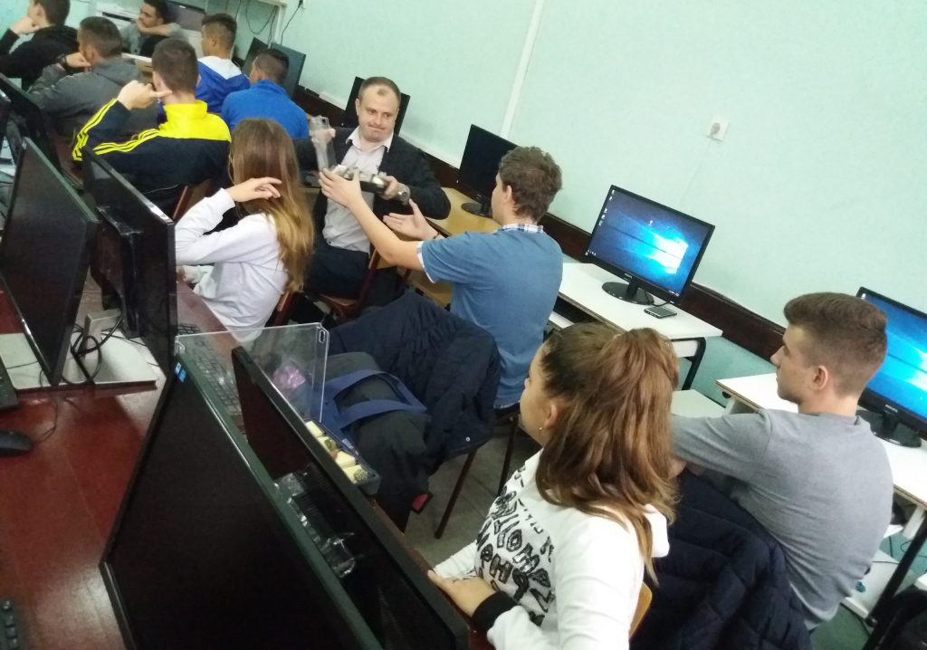 Twelve students sitting behind computer screens in a classroom.