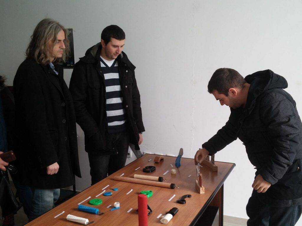 Four people standing indoor and looking at objects placed on a table illustrating project
