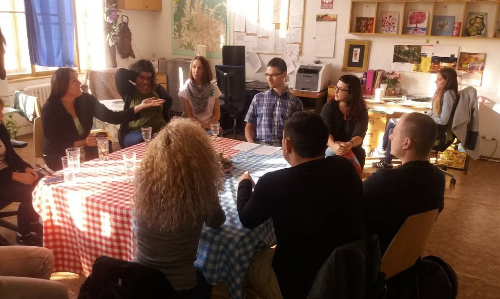 Nine people sitting at a table in a living room.